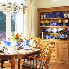 I normally love a bit more of a modern look, but the rustic warmth of the wooden hutch wiht the table and chairs with just a hint of bold with the royal blue all creates a very real space.