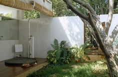 White Modern-Tropical Bathroom  An outdoor bathroom separated from a garden by bamboo blinds.
