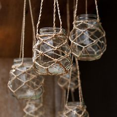 Jar tea light hanging lanterns with nets for nautical charm. They're no longer available, but Martha Stewart has a great tutorial how to knot nets around glass jars (or vases). Here: http://www.marthastewart.com/900617/knotted-hanging-lantern-how