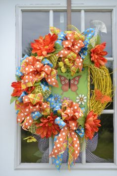 Welcome Butterfly Wreath. ETSY.com. Yellow painted grapevine wreath, Yellow Soft deco mesh, metal sign with an orange butterfly, WELCOME written above it, flowers on the bottom in white, blues and pinks. I added 4 large orange daisy's, yellow floating butterflies,rtibbons, blue with flowers, yellow with orange,blue,white,and pink stripes. a glittered orange butterfly off to the side.