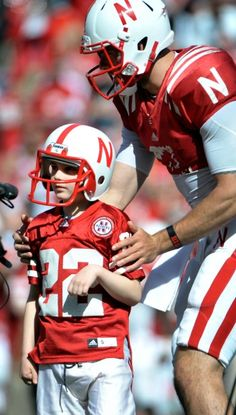 Taylor Martinez (3) guides Jack Hoffman to the right spot for his play in the second half of the Nebraska Red-White spring football game at Memorial Stadium. More than 2 million people have watched the play on YouTube. Jack, 7, has battled brain cancer for the past two years.