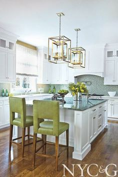 Wrought-iron pendants from Troy Lighting and Ann Sacks glass tile accentuate a green and white kitchen | New York Cottages & Gardens | April 2014