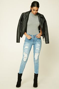 A pair of skinny jeans featuring a destroyed look, mock zippers, a five-pocket construction, a mid-rise waist, and a zipper fly.
