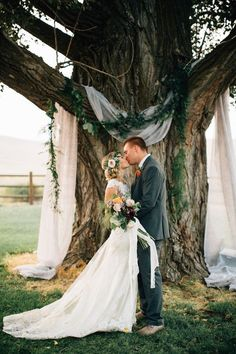 We often hear brides & grooms say they don't want lots of detail so as not to detract from the natural beauty; but we think the opposite. This is a perfect example of an inexpensive, beautiful detail that adds SO much to the tree as a ceremony backdrop. The greenery garland is something your florist can make so easily and the couple is framed perfectly by the white linen (which also catches the light and makes the color variation in the trunk pop).