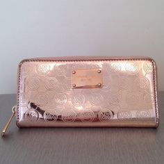 Michael Kors rose gold metallic wallet Michael Kors rose gold monogram mirror metallic wallet. Gently used..only carried a couple of times. *NOTE: Faint scratch marks on the leather and there is slight scratching on logo plate as shown in last picture.. so hard to photograph bc of mirror-like finish..still gorgeous!* Open to reasonable offers! Michael Kors Bags Wallets