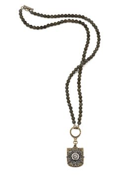 """32"""" faceted green labradorite with antiqued brass-clad FK hoop and small shield bezel and antiqued sterling silver-clad Honour medallion by French Kande"""