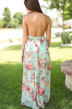 Rear view of woman wearing an open back floor length mint green with pink flowers dress that is lined to the knee