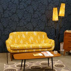 So retro! Fantastic yellow mode-century love seat with dark blue patterned walls.