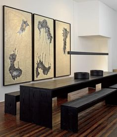 Avant-Garde Home of Lukas Machnik and Lonney H. White III: A long table and matching benches define the dining area in a wide hallway. White's dramatic paintings incorporate encaustic, thread, and metal alloy spills.