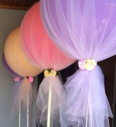 Balloons wrapped in tulle. Would be really cute as giant lollipops for a kid's birthday.