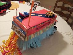 """""""Fiesta Float"""" (front) mounted on a huge monster car, just a shoebox decorated, with some velcro to hold the cars on top. Hotwheels plate was a dollar store special. Pull string in front!"""