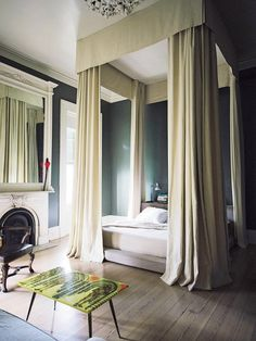 Bedroom with a sky-high bed canopy and low platform bed and  a spectrum of deep green hues