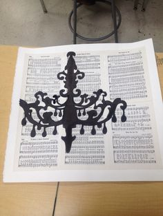 One of my art projects. Modge podge old hymnals to water color paper and silhouette of chandelier in black ink.