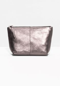 This spacious clutch is styled from supple leather with a clackered metallic finish for a modern, slightly worn-in look.