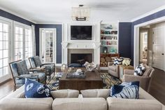 Traditional Home | Deep blue walls and accents in the family room of this Hamptons home are a nod to the nearby ocean
