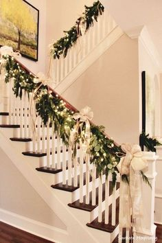 Parade of Homes Nashville Area natural garland, white lights, gold bows draped on handrail of staircase.natural garland, white lights, gold bows draped on handrail of staircase.