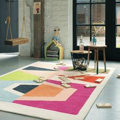 Totem Rugs 78502 from the Xian range feature a stylish retro design with pink, red, blue and green colour tones and a neutral ivory border which work superbly together to enhance any modern room setting.