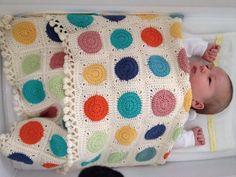 Crochet spotty baby blanket with little tassel border.