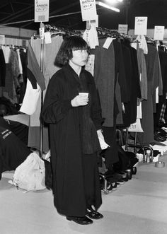 Rei Kawakubo, backstage at her spring 1986 fashion show wearing her own black ensemble and flat shoes.