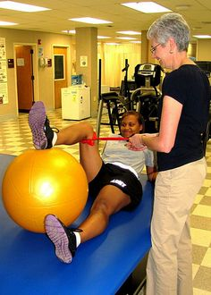 At 9 a.m., July 27, Marge Bessler, an athletic trainer in the Physical Therapy Clinic, engages Kelly McGalliard in various quad strengthening exercises during her physical therapy appointment. Here, the Soldier uses an inflated physio ball to strengthen her leg. McGalliard is one of many active duty Soldiers attempting to recover from a sustained injury. (Photo by Marlon J. Martin, McDonald Army Health Center, Fort Eustis, Va.)