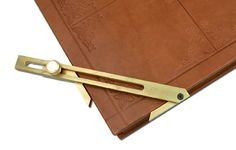 """Corner square. A bookbinding tool used for transferring measurements to corners. Aluminum with a brass screw. Length: 8""""."""
