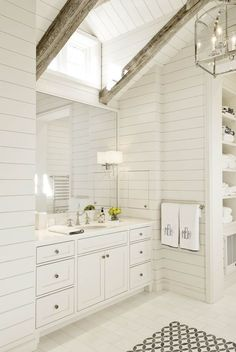 White master bathroom features a shiplap vaulted ceiling dotted with rustic wood beams accented with an Arch Top Lantern illuminating a black and white tiled floor placed in front of a white vanity and a white framed mirror. Coastal Bathroom Decor, Beach House Bathroom, Nautical Bathrooms, Attic Bathroom, Small Bathroom, Attic Shower, Bathroom Vintage, Bad Inspiration, Bathroom Inspiration