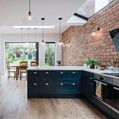 love the brick wall and big windows with the black cabinets in this kitchen #industrialkitchen