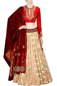 Featuring a dupion base appliqued red and peach floral bridal lehenga choli and a velvet dupatta with gold and silver embellishments.