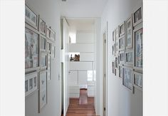 Pintada com tinta azul, a parede deste apê, assinado pela arquiteta Andrea Murao, é repleta de fotos de família. Entre os retratos, toques de humor: cabeça de alce e asas
