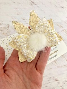 "Easter bunny ear bow. This bow is approx 3.5"" in size made from a gold textured fabric with lemon glitter. Comes with a faux Pom Pom and bunny ears This bow can come customised on headband or clip Item details. Headband we use are soft nylon headband one size fits all. Clips"