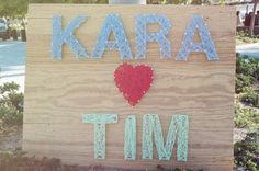 wooden sign with threaded bride + groom names
