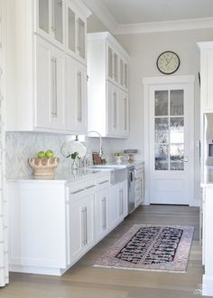 10 simple tips for styling the kitchen counters white modern farmhouse kitchen white shaker cabinets white carrar marble marble counters and herringbone backsplash kitchen countertop decor-1