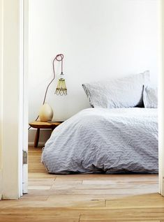attach a hook into the wall to coil up a long corded light-voila. bedside light!