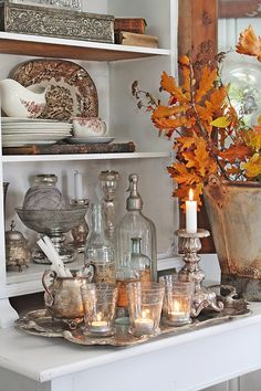 A collection of silver, plates and glass, a silver tray and branches in autumn colors on a white cupboard. VIBEKE DESIGN