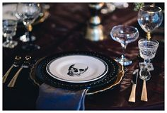Skull plates, Burgundy linens and matte gold flatware for this dark, halloween inspired wedding.