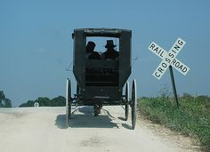 An Amish couple in Ethridge, TN, about to cautiously cross the railroad track that runs north and south through Ethridge, Tn.