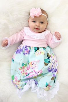 This sweet pink, purple & aqua floral layette gown is the perfect going home outfit for your baby girl! The elastic ruffle bottom makes diaper changes super easy any time of day or night and not to me