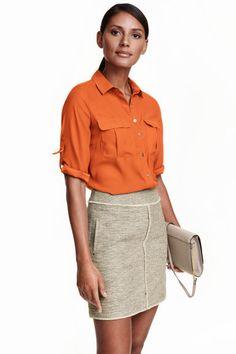 Falda corta: Falda corta de tela con bolsillos laterales de parche y cremallera visible de metal detrás. Sin forrar.
