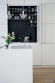 Zwart wit contrast in afsluitbare pantrykast in moderne keuken...
