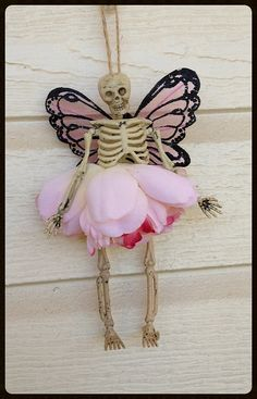 Halloween decoration A six inch skeleton is wearing a flower petal skirt. She has a pair of pink fairy wings. Will look great hanging from a feather tree. Halloween ornament