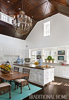 Crowned with a dramatic vaulted, stained-wood ceiling, the kitchen features white shiplap walls, an island topped with a single piece of wood found in upstate New York, and wicker furniture. - Photo: Eric Roth / Design: Susan Zises Green