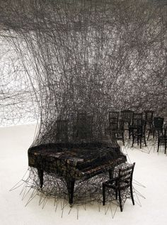 """Photography of an installation created by Japanese artist Chiharu Shiota.    /// The installation, named """" In Silence"""", was inspired by one of the artist's personal traumatic memories as a child, having witnessed her neighbor's house burning down. The pieces tangled up in black thread are echoing a sketch-like imagery and the burnt piano is in fact a direct memory of the artist, as it resembles her neighbor's piano blazed up in smoke."""
