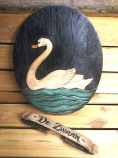 De zwaan. Het houten tekstlint er onder, kan eenvoudig over de bovenkant van het bord geschoven worden. RAWdecorations.com heeft het geheel met de hand gemaakt.