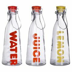 "Adorned with bright labels, these 3 glass bottles add a colorful pop to breakfast or lunch.  Product: 3 Piece bottle setConstruction Material: Glass and metalColor: MultiFeatures: 32 Ounce capacity Dimensions: 14"" H x 2"" Diameter Cleaning and Care: Hand wash"