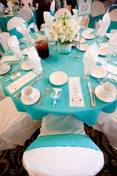 Tiffany blue turquoise guest table setup complete with wedding programs, white chocolate party favors and bling flower centerpiece.