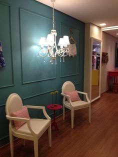 Loja Roupa feminina por Amis Arquitetura - parede com molduras pintadas em verde, lustre clássico de cristal e cadeiras Louis Ghost brancas
