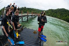 PADI Instructor Mel briefs his students how important it is to keep hold of the regulator in their mouth when they perform their deep water entry.