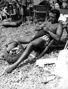 Ugo Tognazzi ( Italian film, TV, and theatre actor, director, and screenwriter) knitting on the beach