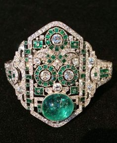 An Art Deco diamond and cabochon bracelet, circa 1930. The openwork bracelet with a lozenge-shaped central plaque with geometric patterns, set with brilliant-cut diamonds, cabochon emerald and calibré emeralds.