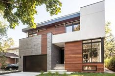 This two-storey custom-built modern home has a façade that combines stucco, brick and Ipe wood siding, and features a slightly sloped roof, a front two-storey balcony and a built-in garage. Stucco Exterior, Stucco Homes, Building Exterior, Modern House Facades, Garage Door Design, Garage Doors, Ipe Wood, Brick And Wood, Modern Contemporary Homes